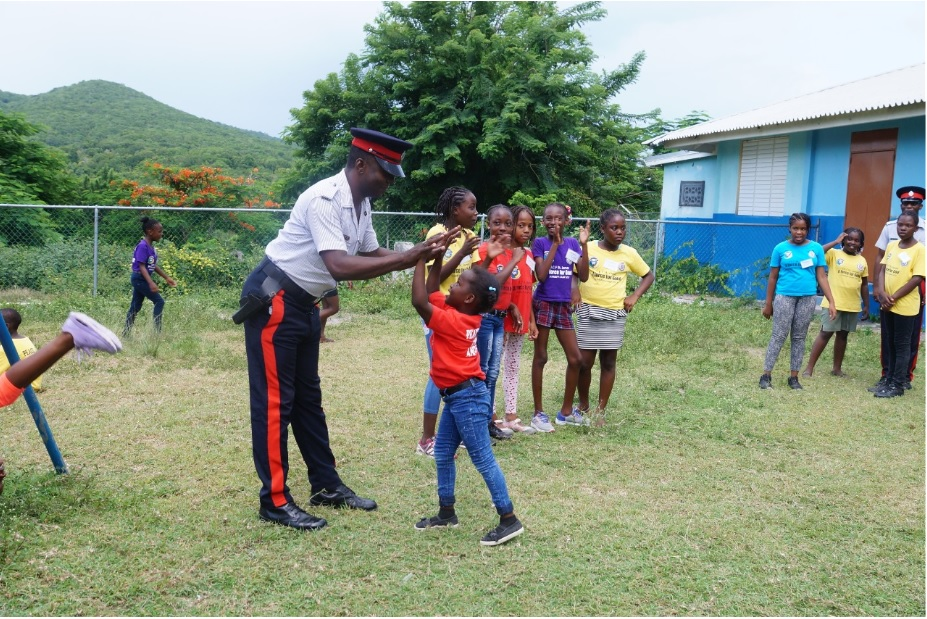 A police officer interacting with children in Salt Spring, St James