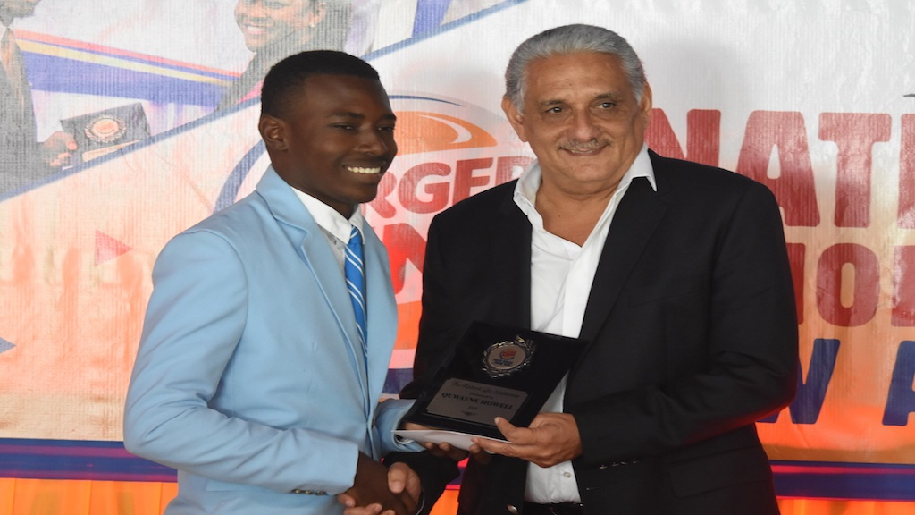 Richard Lake (right) of Restaurant Associates Limited, the Jamaican franchise holder of Burger King, makes a presentation to Rodwell Lake Scholarship recipient Quwayne Howell of St George's College. (PHOTOS: Marlon Reid)