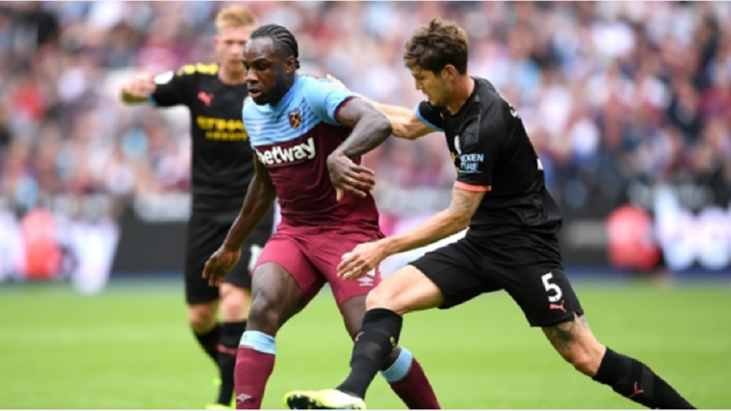 John Stones (right) of Manchester City challenges West Ham's Michail Antonio.