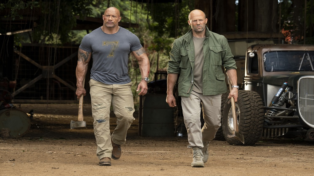 "This image released by Universal Pictures shows Dwayne Johnson, left, and Jason Statham in a scene from ""Fast & Furious Presents: Hobbs & Shaw."" Movie going audiences have helped the ""Fast & Furious"" spinoff ""Hobbs & Shaw"" take another lap at No. 1 even with the onslaught of new movies last weekend. (Frank Masi/Universal Pictures via AP)"