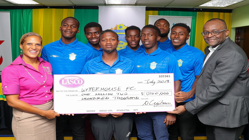 Danielle Cunningham (left), beverage marketing manager, LASCO Distributors, presents a cheque for $1.2 million to Donovan White (right), president of Waterhouse FC, at a recent media briefing ahead of the Scotiabank Concacaf League match between Waterhouse and HS Herediano of Costa Rica. Sharing in the moment are Waterhouse head coach Marcel Gayle (fourth left) and several players.