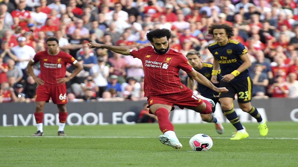Liverpool's Mohamed Salah scores his side's second goal of the game from the penalty spot during the English Premier League football match against Arsenal at Anfield, Liverpool, England, Saturday Aug. 24, 2019. (Anthony Devlin/PA via AP)