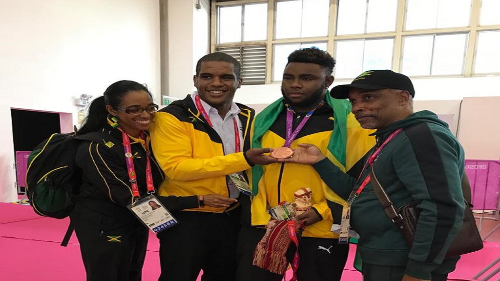 Theador Subba with President of the Jamaica Paralympic Association (JPA), Christopher Samuda and coach Steven Moore hold Subba's medal while JPA Secretary General Suzanne Harris-Henry looks on.