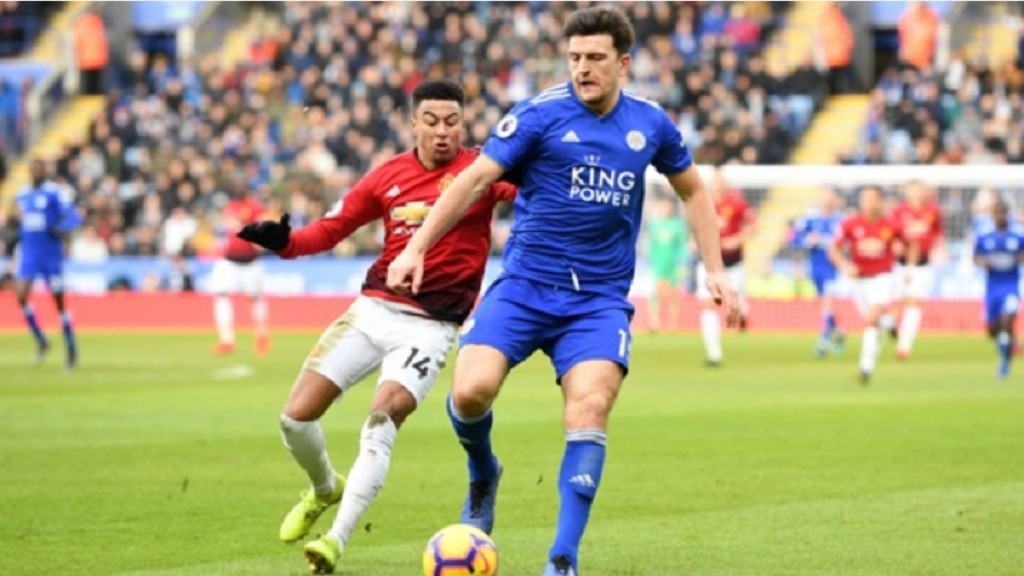 Harry Maguire shields the ball from Jesse Lingard.