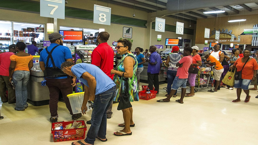 Residents stand in line at a grocery store as they prepare for the arrival of Tropical Storm Dorian, in Bridgetown, Barbados, Monday, August 26, 2019. Much of the eastern Caribbean island of Barbados shut down on Monday as Dorian approached the region and gathered strength, threatening to turn into a small hurricane that forecasters said could affect the northern Windward islands and Puerto Rico in upcoming days. (AP Photo/Chris Brandis)