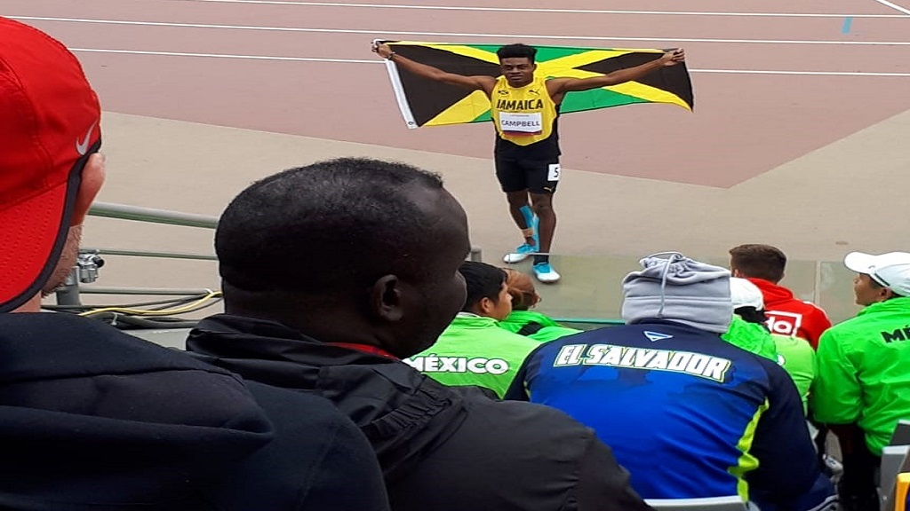 Team captain, Chadwick Campbell celebrates with the Jamaica flag following his silver medal in the T13 100m at the 2019 Parapan American Games in Lima, Peru on Monday, August 26, 2019.