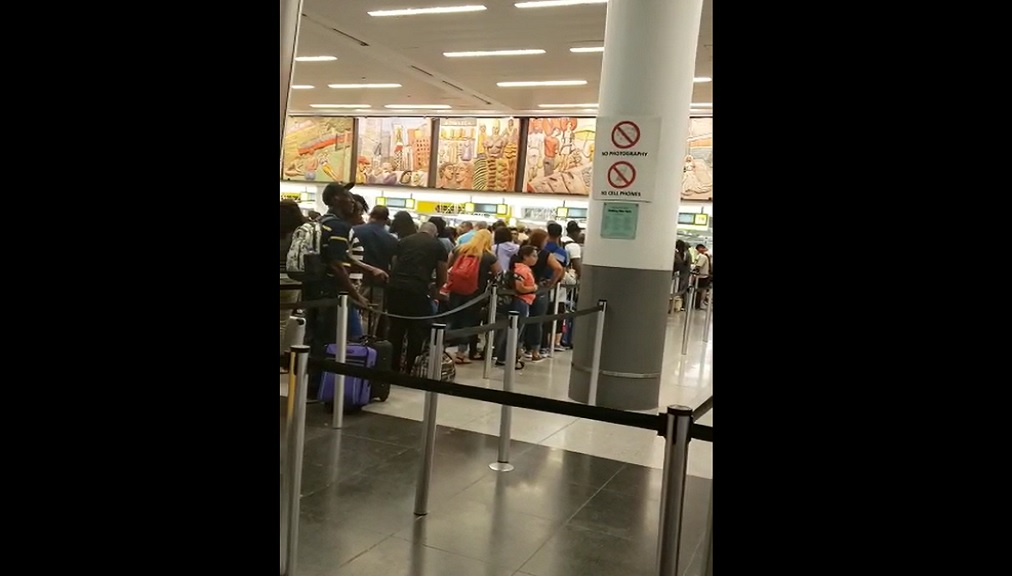 Photo: Group of Jamaicans and other Caribbean nationals wait in line at JFK airport on Friday.
