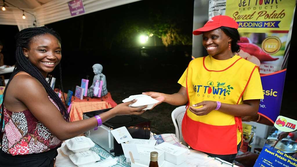Doneille Derrett, an employee at the JTFA, (right) sells a slice of her enterprise's traditional sweet potato pudding to an attendee at Kingston Kitchen.