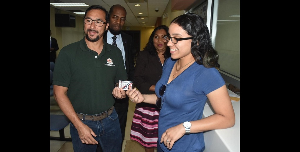 Flashback: National Security Minister Stuart Young  presents a Venezuelan National with her Registration Card. Photo: National Security Ministry.