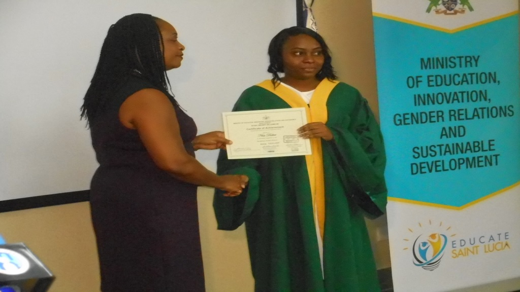 A member of staff receiving her certificate from Kathleen Valcin of the Ministry of Education
