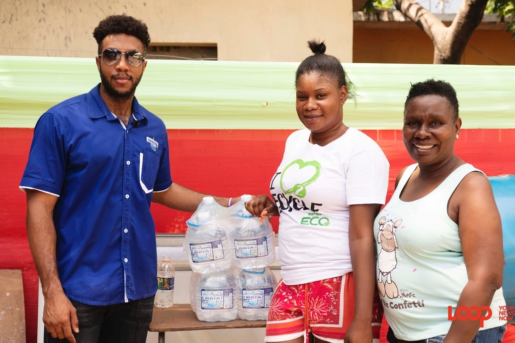 Mikhail Russell  (left) Digital Media Coordinator at Wisynco shares a moment with Red Hills residents Tawanda Archer and Charmaine Baker at a recent distribution event.