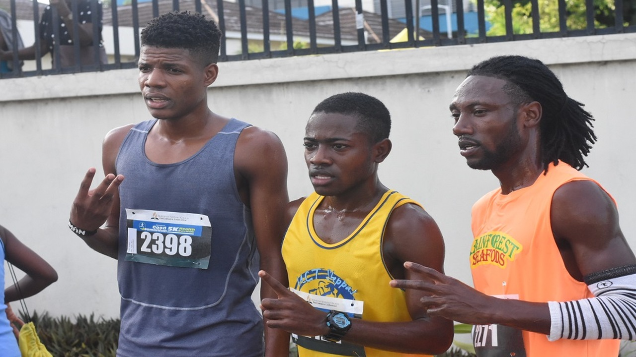 Winner of the Good Samaritan Run, Henry Thomas (centre) of UCT Steppas pose with runner-ups, Kemar Leslie (right) of Rainforest Seafoods, and Kosiani Dunkley of Riot Squad after the race on Sunday. (PHOTOS: Marlon Reid)