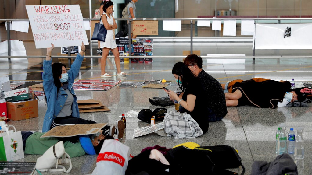 A protester shows a placard to travellers as they continue their sit-in rally at the airport in Hong Kong, Wednesday, Aug. 14, 2019.  (AP Photo/Vincent Thian)