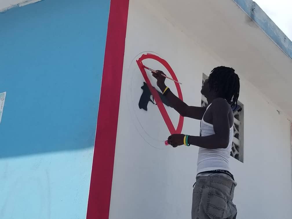 Un homme dessine sur un mur à Cité Soleil