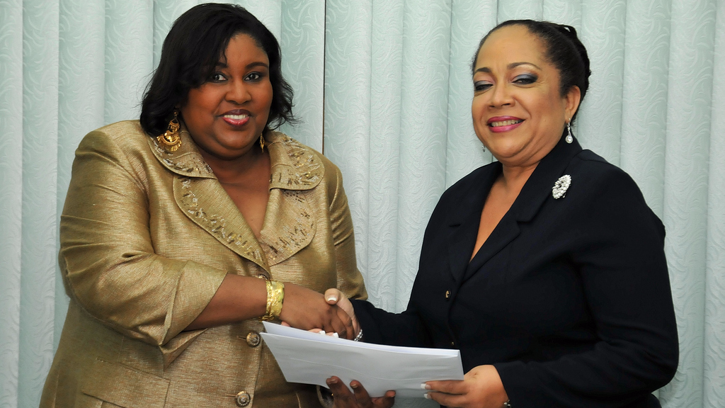 In this January 2010 photo then Minister of Community Development, Culture and Gender Affairs Marlene McDonald (Left) presents the instrument of appointment to chairman of the NTC Denyse Gouveia. (GISL)