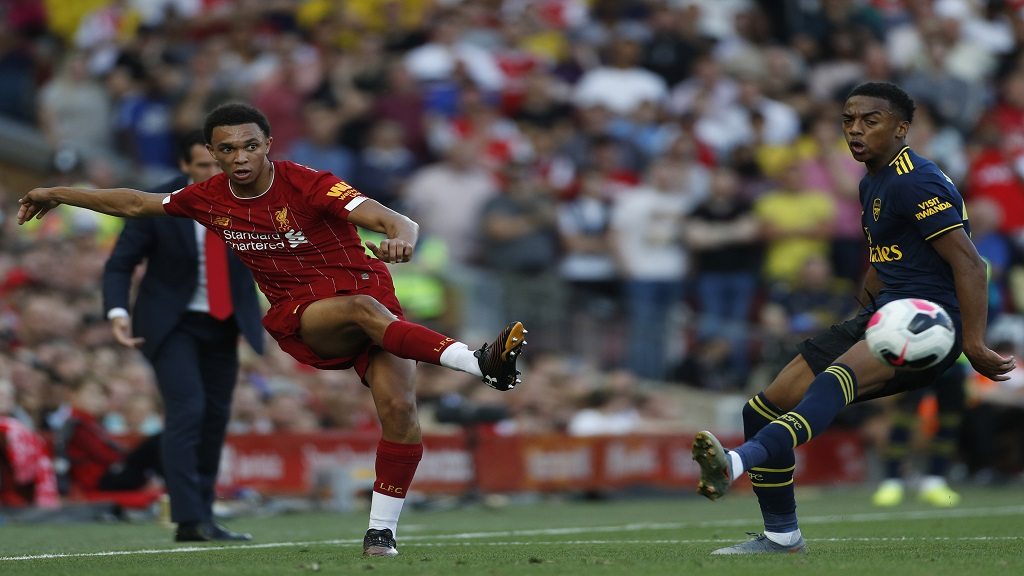 Liverpool's Trent Alexander-Arnold, left, passes the ball past Arsenal's Joe Willock during the English Premier League football match at Anfield stadium in Liverpool, England, Saturday, Aug. 24, 2019. (AP Photo/Rui Vieira).