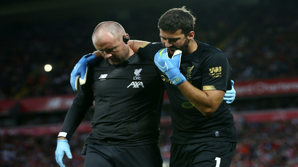 Liverpool's goalkeeper Alisson Becker, right, reacts as he leaves the pitch after an injury during the English Premier League football match against Norwich City at Anfield in Liverpool, England, Friday, Aug. 9, 2019. (AP Photo/Dave Thompson).