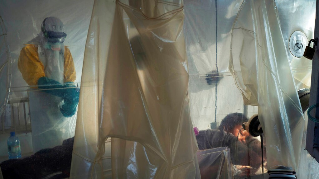 In this July 13, 2019 file photo, health workers wearing protective gear check on a patient isolated in a plastic cube at an Ebola treatment center in Beni, Congo. (AP Photo/Jerome Delay, File)
