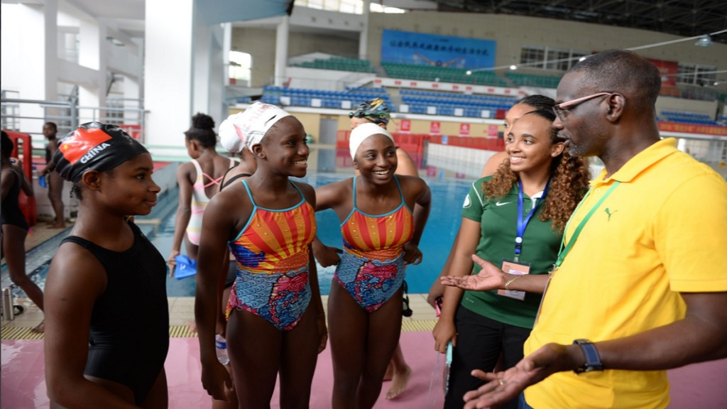 Permanent Secretary in the Ministry of Culture, Gender, Entertainment and Sport, Denzil Thorpe (right), speaks with Jamaican coach, Rachell Minto-Walker (second right), and three of the winning synchronised swimming team members (from left): Ajoni Llewellyn, Laila Bailey and Nyouka Baugh in China.