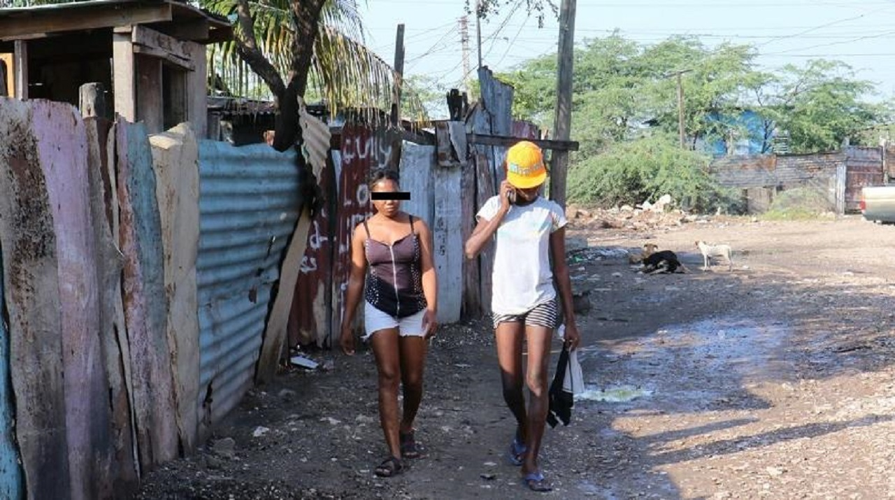 Women walk amid zinc fencing in an inner-city community in Jamaica.