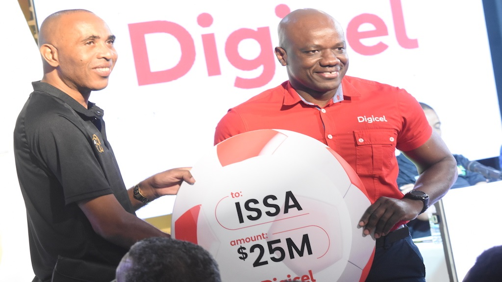Elon Parkinson (right), PR & Communications Manager at Digicel, presents a symbolic cheque to Keith Wellington, president of ISSA during the launch of the 2019 schoolboy football season on Wednesday, August 21 at the Terra Nova All Suite Hotel. (PHOTOS: Marlon Reid).
