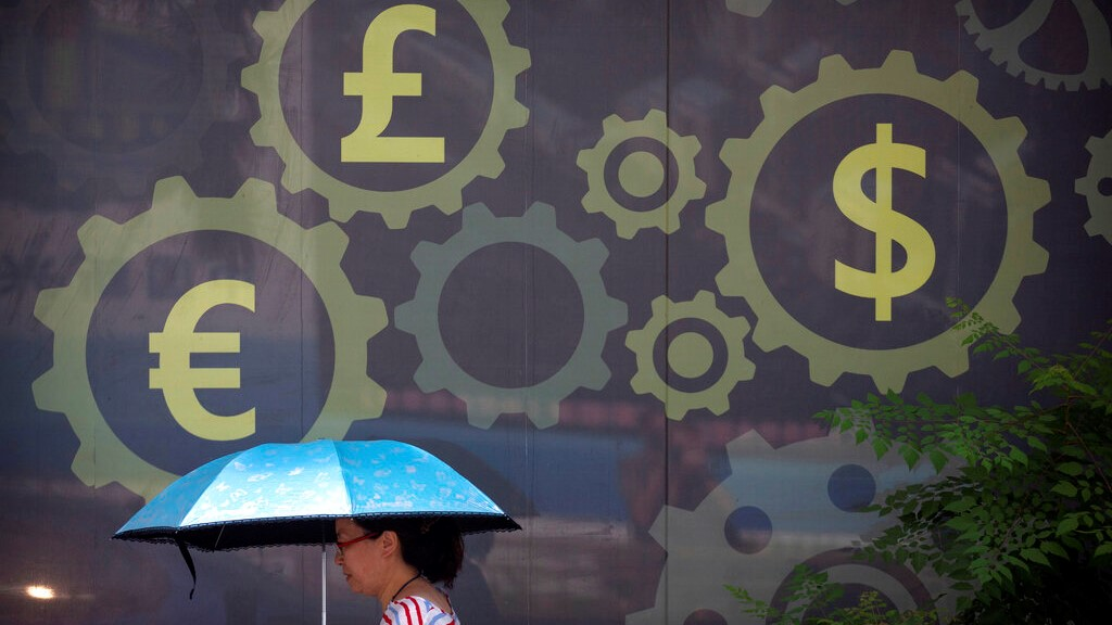 In this July 20, 2018, photo, a woman carries an umbrella as she walks past a mural displaying world currency symbols outside of a bank in Beijing. (AP Photo/Mark Schiefelbein)
