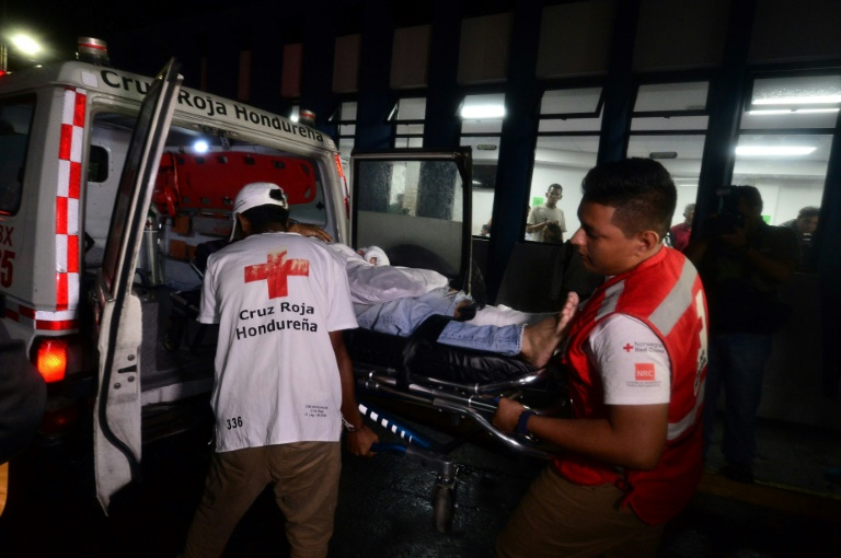 Des médecins de la Croix-Rouge hondurienne entourent un blessé devant l'hôpital Escuela à Tegucigalpa, le 17 août 2019