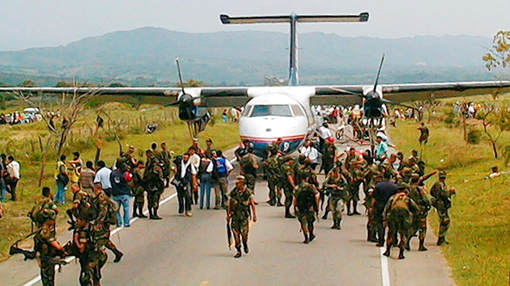 In this Feb. 20, 2002 file photo, soldiers surround an airliner hijacked by rebels of the Revolutionary Armed Forces of Colombia, FARC, that was forced to land in a rural area near Hobo, in the southern Neiva state. (AP Photo/Alejandro Saavedra, El Diario del Huila, File)
