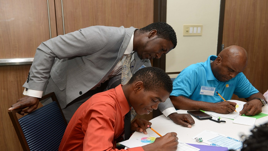 SOS Children's Village Director, Marvin Simpson (standing) guides a participant at the IGT Career Development Workshop in completing his course activity. Also pictured, Owen Campbell, Driver, IGT (right).