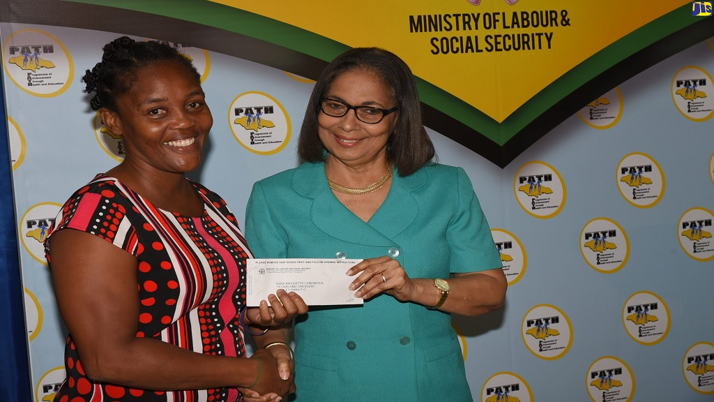 Minister of Labour and Social Security, Shahine Robinson (right) presents mother of five, Sara Lemonious, with a cheque. The occasion was the handover of cheques under the Ministry's Back-to-School grant for PATH beneficiaries on Friday at the Ministry, in Kingston.  (PHOTO: JIS)