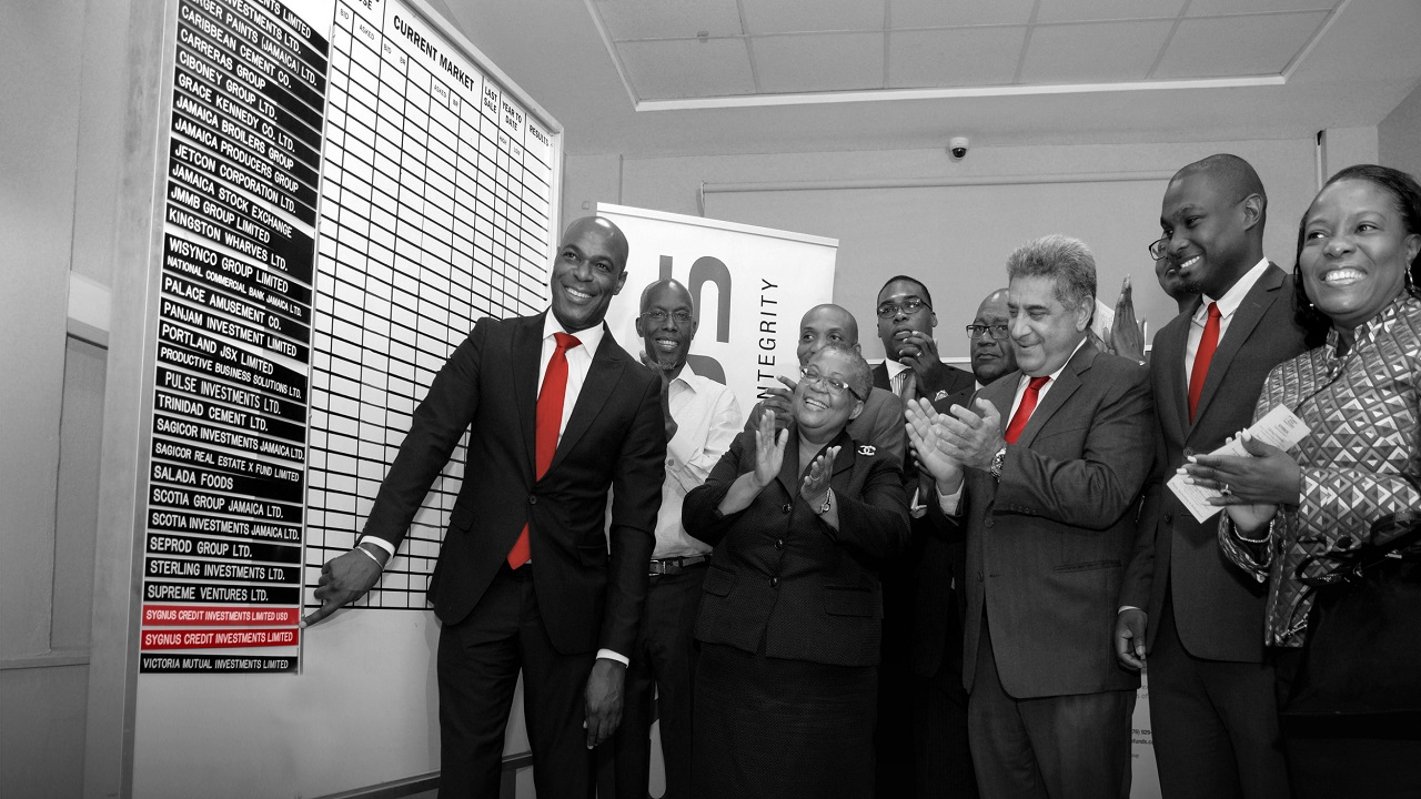 In this June 2018 file photo, Berisford Grey - Co-Founder & CEO of Sygnus Capital, places his company's name card on the Jamaica Stock Exchange's trading boarding during a listing ceremony.