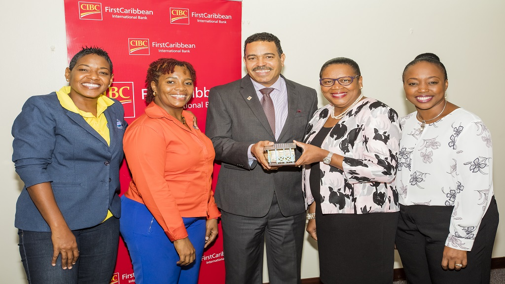 Nigel Holness (centre), Managing Director and Jerome Griffith (2nd right), HR Manager of the bank hold a model house presented to the team by Food For The Poor Executives, Marsha Burrell Rose (left), Development & Marketing Manager and Kivette Silvera, Financial Controller. At right is Renee Whitehorne, the bank's Marketing Manager.