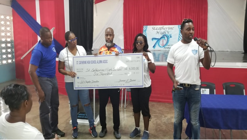 St Catherine High School's principal, Marlon Campbell (left), accepts the Class of 1989 symbolic checque of $1m from Anthony Johnson during a handing over function at the institution recently. The funds will go towards the state-of-the-art auditorium that is being built on the compound.