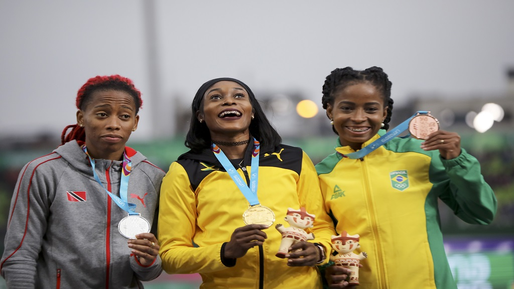 Gold medalist Elaine Thompson of Jamaica, centre, silver medalist Michelle-Lee Ahye of Trinidad and Tobago, left, and bronze Vitoria Cristina Silva of Brazil pose for photos at the podium for the women's 100m during the athletics at the Pan American Games in Lima, Peru, Wednesday, Aug. 7, 2019. (AP Photo/Rodrigo Abd).