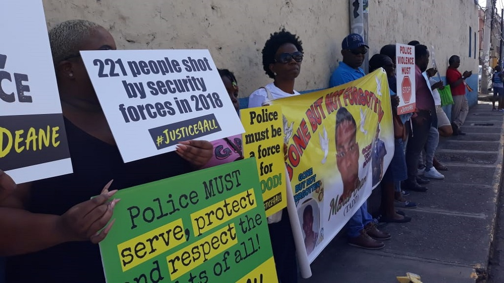 Mercia Fraser (third right) behind a banner  bearing the image of her late son, Mario Deane, as she led a protest in front of the Barnett Police Station on the fifth anniversary of Deane's beating death.