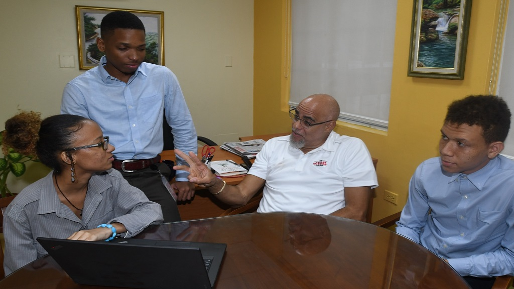 An animated Keith Duncan, JMMB Group CEO (second right, seated) makes a point to  JMMB Group summer interns (from left) Imani Miller, Kashkayde Matthews, while Chadwill Miller looks on,  during the rap session at the company's head office.