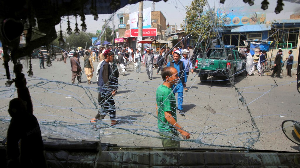 Afghans are seen through a shattered glass of a transport bus broken after an explosion in Kabul, Afghanistan, Wednesday, Aug. 7, 2019. (AP Photo/Rafiq Maqbool)