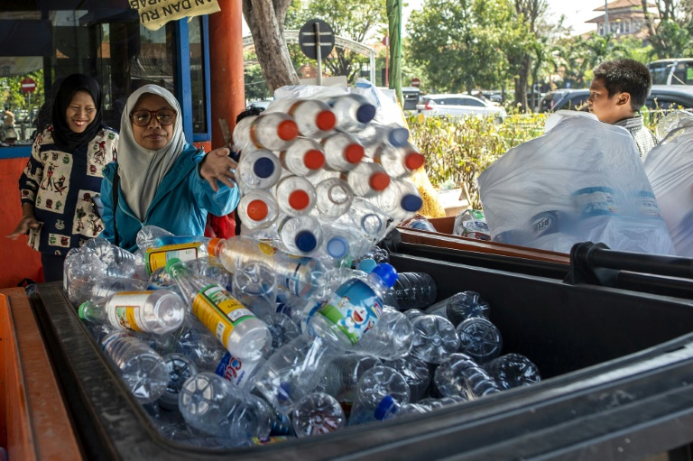 Des dizaines de personnes échangent des bouteilles en plastique contre des tickets à la gare routière de Surabaya, en Indonésie, le 21 juillet 2019