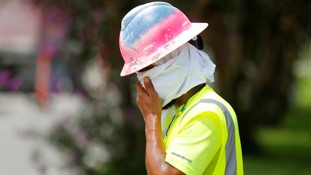 Construction worker Dineose Vargas wipes his face at a construction site on the Duncan Canal in Kenner, La., Tuesday, Aug. 13, 2019. (AP Photo/Gerald Herbert)