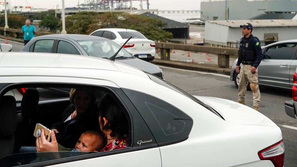A woman sits in a car with a baby as they wait on a blocked access as a Federal Highway Police officer stands next at the busy bridge connecting the city of Niteroi to Rio de Janeiro , Brazil, Tuesday, Aug. 20, 2019 during a hostage standoff. (AP Photo/Leo Correa)
