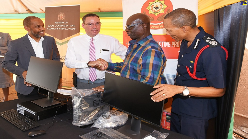 Minister without Portfolio, Daryl Vaz (second left), officially hands over 33 desktop computers to Local Government Minister, Desmond McKenzie, at the Local Government Ministry in St Andrew, for the creation of a local bus fire warning index. Looking on (l-r) are: Director of the Met Service, Evan Thompson; and Jamaica Fire Brigade Commissioner, Stewart Beckford.