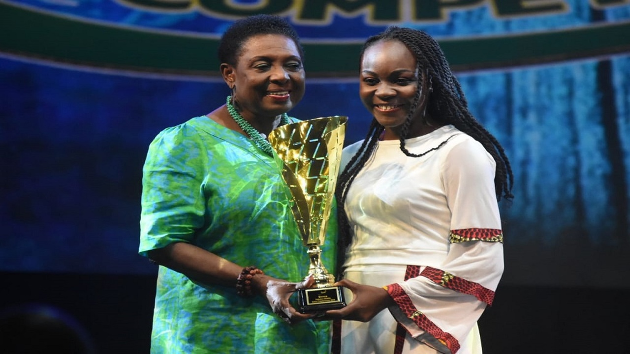 Joanna Walker (right), the winner of the 2019 Jamaica Gospel Song Competition, is awarded the champion's trophy by Culture Minister Olivia Grange on Sunday at the National Arena. (PHOTOS: Marlon Reid)