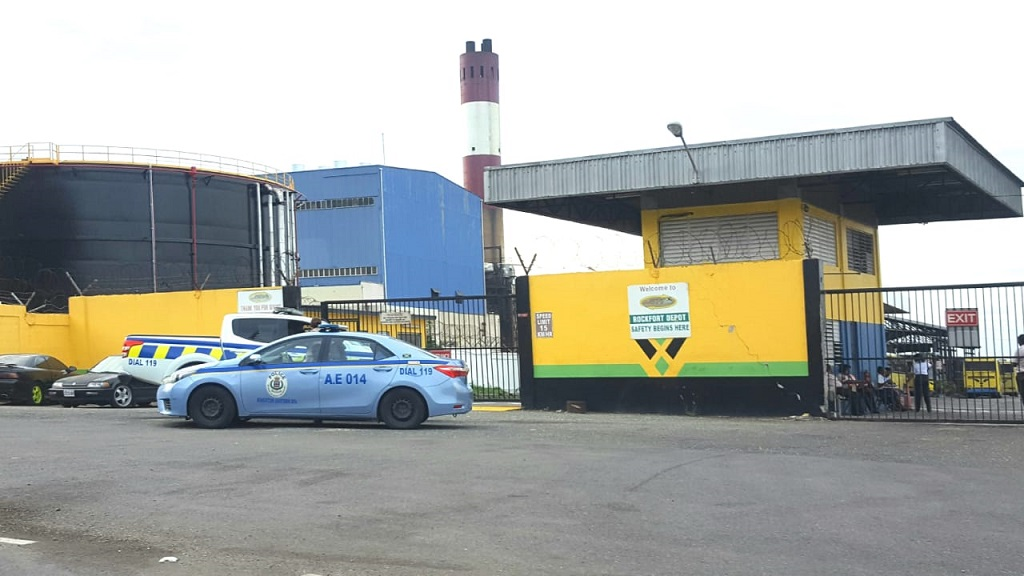 A police service vehicles parks at the gate of the JUTC depot in Rockfort on Wednesday morning.