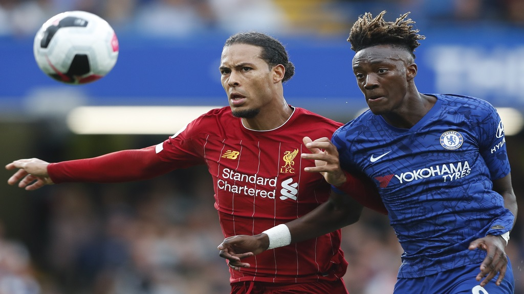 Liverpool's Virgil van Dijk, left, and Chelsea's Tammy Abraham go for the ball during their English Premier League football at the Stamford Bridge Stadium, London, Sunday, Sept. 22, 2019. (AP Photo/Frank Augstein).