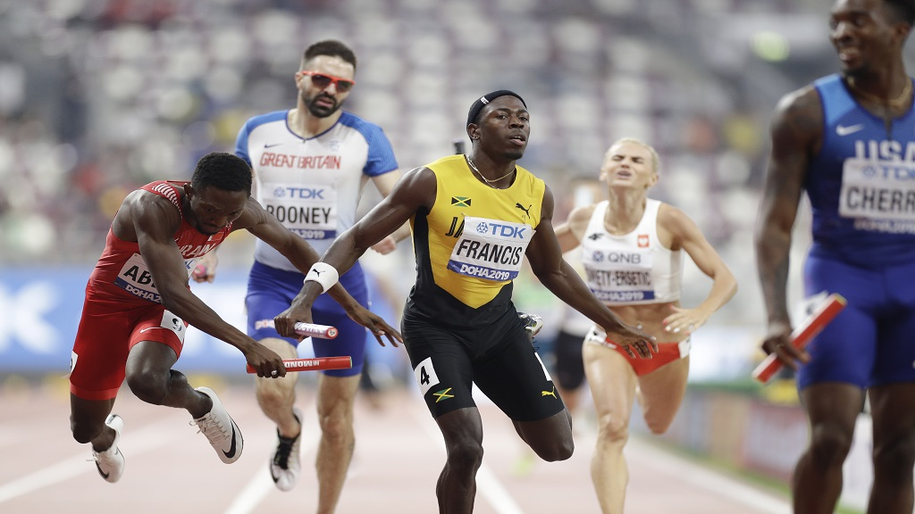 Bahrain's Abbas Abubakar, left, and Jamaica's Javon Francis run the last leg in the mixed 4x400m relay race at the World Athletics Championships in Doha, Qatar, Sunday, Sept. 29, 2019. (AP Photo/Petr David Josek).
