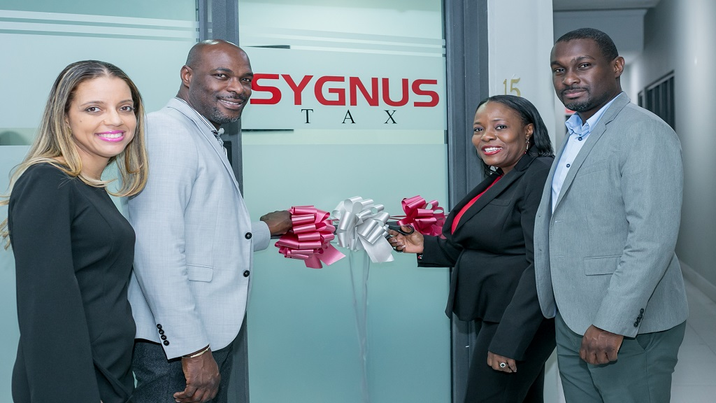 In this file photo, Elizabeth James, Head of Wealth Management, Sygnus Capital, Berisford Gray, Chief Executive Officer, Dionnie Headley, Managing Director, Sygnus Tax and Ike Johnson, Chief Operating Officer, Sygnus Capital pose for a photo during the opening of the Sygnus Tax Office.