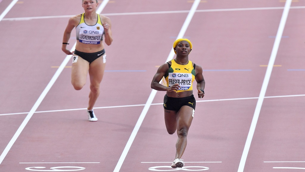 Shelly-Ann Fraser-Pryce, of Jamaica, crosses the finish line followed by Gina Lückenkemper, of Germany, left, in a women's 100m  race heat during the World Athletics Championships in Doha, Qatar, Saturday, Sept. 28, 2019. (AP Photo/Martin Meissner).