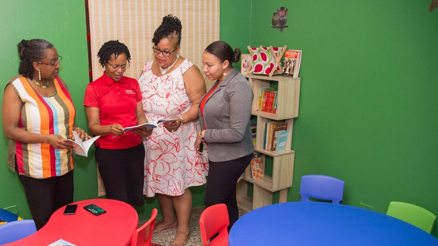 Alicia Hospedales, Digicel Foundation Strategic Partnership Officer (2nd from left) reviews one of the books at the newly opened Reading Room. Also sharing in the moment are Raisa Belcon, Secretary of the Beausejour Community Council (from left) Susan Hong, Chairman of the Diego Martin Regional Corporation and Elizabeth Belcon, President of the Beausejour Community Council.