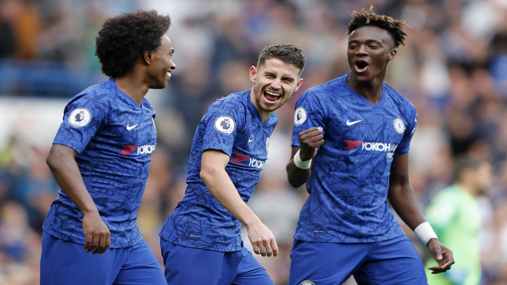 Jorginho (centre) of Chelsea celebrates with teammates Tammy Abraham, right, and Willian after scoring the first goal during the English Premier League football match against Brighton & Hove Albion at Stamford Bridge stadium in London, Saturday, Sept. 28, 2019.(AP Photo/Frank Augstein).