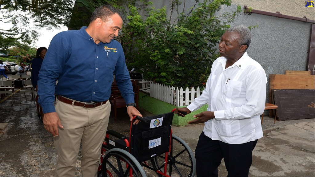 Health and Wellness Minister, Dr Christopher Tufton (left), and Past President of the Rotary Club of St Andrew and Chairman of the club's Wheelchair Project Committee, Lloyd Eubank-Green, examine one of 100 wheelchairs that have been donated to the ministry and the Kingston Public Hospital (KPH), at a symbolic handover ceremony on Thursday (September 26) at the skills training institute, Operation Friendship in Kingston.